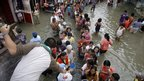 Filipino residents queue in flood waters in Calumpit town, Bulacan province, north of Manila
