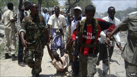 Somalia government soldiers carry an injured man from the scene of a suicide attack in Mogadishu on Tuesday