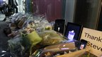 Bouquets of flowers and iPhones and iPads displaying candle graphics are placed in tribute to Steve Jobs outside an Apple store in the Ginza shopping district in Tokyo Thursday - 6 October 2011