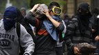 Demonstrators carry stones as they clash with riot policemen during the rally.