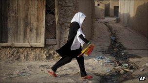 A girl walks through the Sherpur area of Kabul, Afghanistan