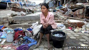 woman sits in front of her damaged house