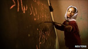 An Afghan girl reads from the board in a home-based school in Kabul in December 2001