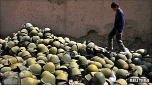 Afghan boy walks next to a pile of Russian-made helmets in the Panjshir Valley