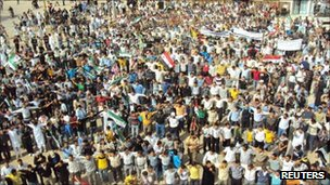 Demonstrators protesting against Syria's President Bashar al-Assad march through the streets after Friday prayers in Homs, in this image provided by a third party