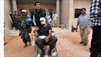 A wounded Libyan NTC fighter is wheeled into the first field hospital near the frontline in Sirte