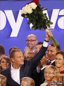 Poland's Prime Minister Donald Tusk waves to supporters after the election results announcement in Warsaw, 9 October 2011