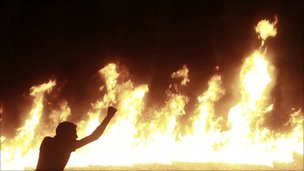 A protester stands near a line of fire during clashes in Cairo