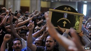 Egyptian Coptic men carry the coffin of a victim of deadly clashes, during a funeral at Abassaiya Cathedral in Cairo on October 10