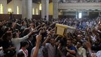 Egyptian Coptic men carry the coffin of a victim of the clashes at Cairo's Abassaiya Cathedral. Photo: 10 October 2011
