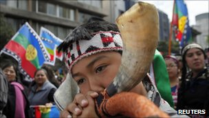 An indigenous Mapuche boy blows a horn during a protest in the Chilean capital, Santiago