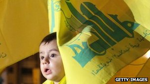 A young boy draped in Hezbollah flags