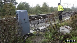 A German policeman stands next to an S-Bahn train track after bottles with flammable liquids were found in Berlin, 11 October.