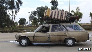 A family flees Sirte by car with possessions loaded on the roof, Libya (11 Oct 2011)