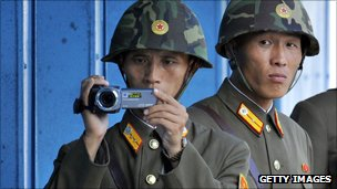 North Korean soldiers look and film footage of the South side of the Demilitarized Zone