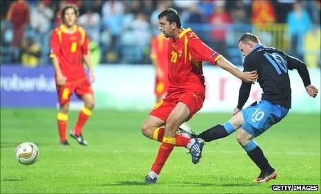Wayne Rooney of England kicks Miodrag Dzudovic of Montenegro