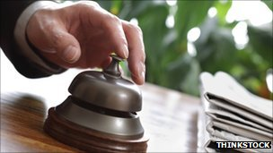 A guest presses a hotel reception bell