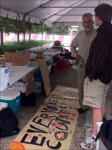 Two men talk at a table at Occupy Nashville