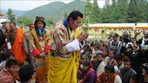 Newly crowned Queen of Bhutan Jetsun Pema (L) and King of Bhutan Jigme Khesar Namgyel Wangchuck (R) acknowledge the crowds after their marriage ceremony at the Dzong monastery in Punakha, Bhutan on October 13, 2011