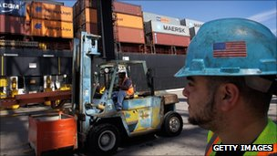 Longshoremen work next to a container ship at Port Everglades