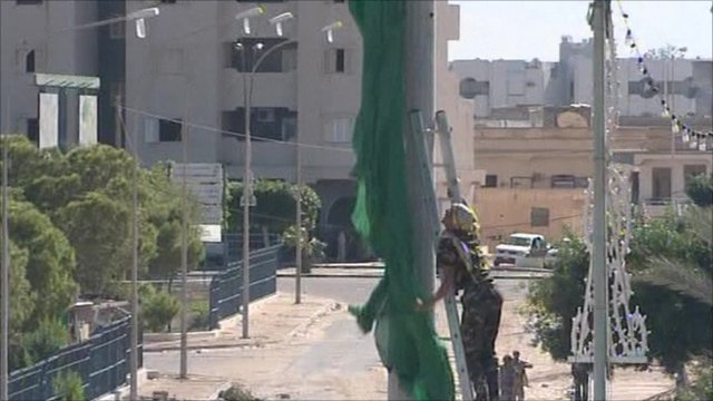 Fighter taking down flag on outskirts of Sirte