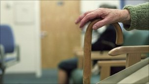 Elderly patient rests her hand on her walking stick in a waiting room
