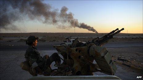 Libyan rebel fighter with burning oil refinery in the distance, Ras Lanuf, August 2011