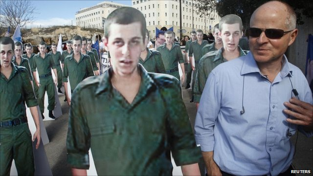 Noam Shalit standing near cardboard cut-outs of his son Gilad Shalit during a protest in Jerusalem