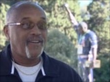 Tommie Smith next to a statue commemorating the black power salute
