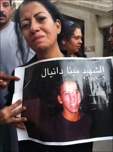 Mary Daniel holds up a picture of her brother Mina Daniel. Photo by Hamada Abu Qammar