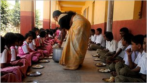 A lady serving food to school kids