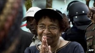 Liberian President Ellen Johnson Sirleaf (C) addresses a crowd of supporters on October 15, 2011 outside offices of her party on the outskirts of Monrovia that had been set alight overnight in a suspected arson attack. 
