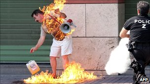 Policeman rushes to extinguish a man who set himself on fire outside a bank in Thessaloniki (September 16, 2011)