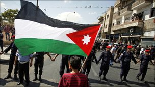 A youth holds a Jordanian national flag as security forces form a human chain at a protest to demand more reforms from King Abdullah in Amman, Jordan, on 9 Sep 2011