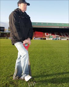 Oval groundsman Sammy Glover tries in vain to make the pitch playable