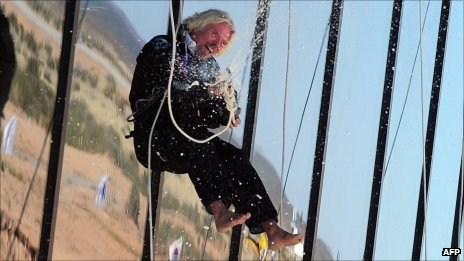 Richard Branson opens a bottle of champagne while abseiling down the side of Spaceport America on 17 October 2011
