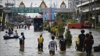 Local residents walk through floodwaters in Pathum Thani province, on 17 October 2011