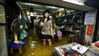 Thai shopkeeper stands in floodwaters at market in Bangkok on 16 October 2011