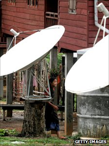 Girl stands by satellite dishes