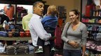 US President Barack Obama holds a child as he buys sweets at the Mast General store in Boone, North Carolina, 17 October 2011