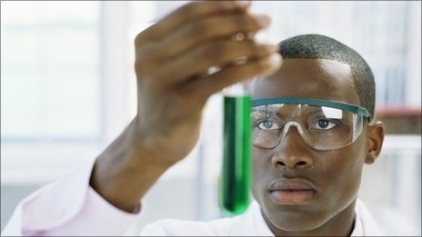 Young man holding a test tube with green liquid