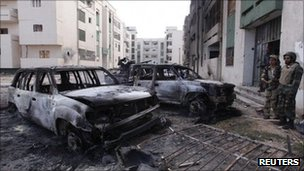 Anti-Gaddafi fighters stand near burnt cars in Sirte. Photo: 18 October 2011