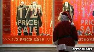 Someone dressed as Father Christmas looking at a pre-Christmas window display