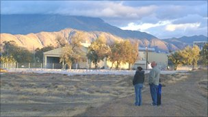 Family stands on a dirt berm overlooking the shuttered town of Empire