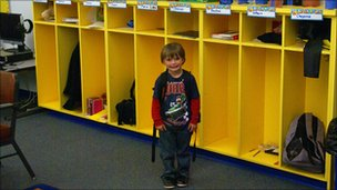 Child stands in front of classroom cubbies