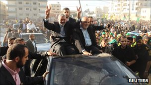 Hamas leader Ismail Haniyeh makes a victory sign as he arrives with some of the freed prisoners at a celebration rally in Gaza City on 18 October 2011