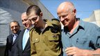 In this handout photo provided by the Israeli Defence Force, freed Israeli soldier Gilad Shalit (2nd R) walks with (L-R) Defence Minister Ehud Barak, Israeli Prime Minister Benjamin Netanyahu his father Naom Shalit at Tel Nof Airbase