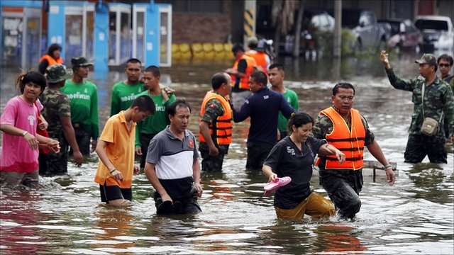 Soldiers help workers and civilians evacuate a flooded area in Thailand