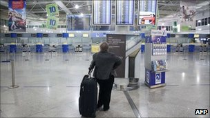 A traveller looks at information boards at the departures hall of Athens' international airport - 19 October 2011
