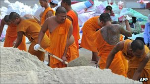 Buddhist monks help fill sandbags in Pathum Thani, Bangkok (19 Oct 2011)